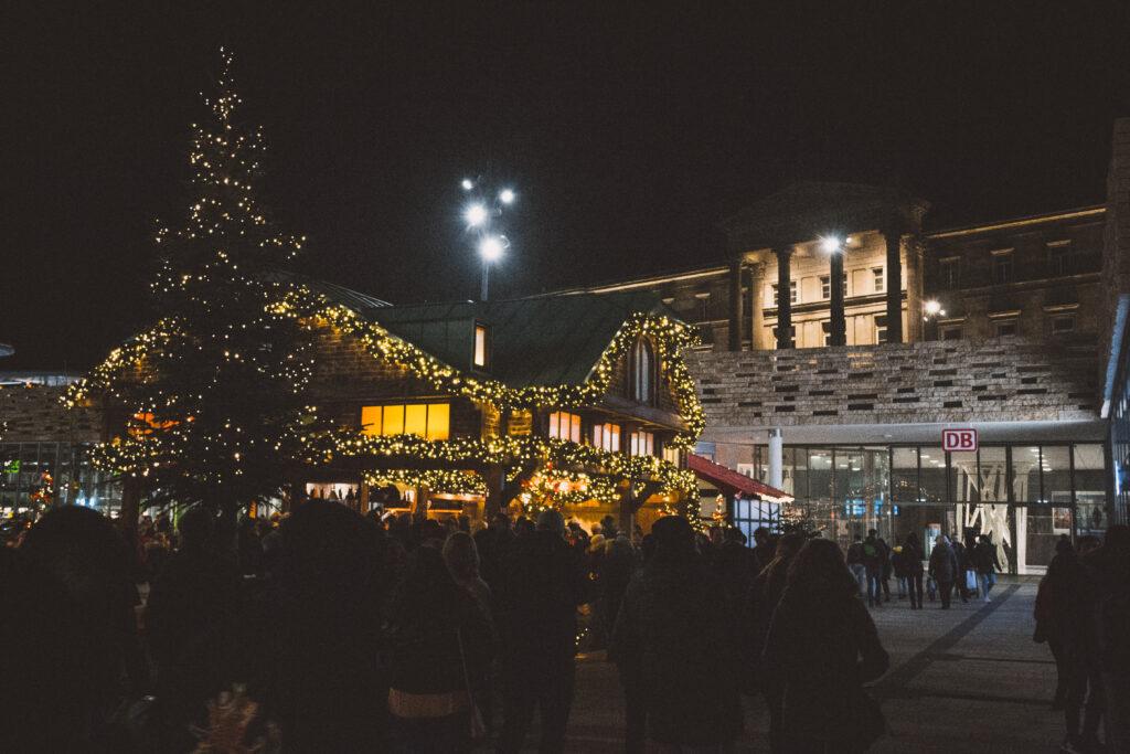 Ein Glühweinstand in Form eines Ziegelsteinhauses mit verkupfertem Dach ist weihnachtlich geschmückt und beleuchtet. Viele Menschen stehen um ihn herum oder gehen rechts an ihm vorbei auf das Bahnhofsgebäude des Wuppertaler Hauptbahnhofs zu. Im Hintergrund leuchtet oberhalb des Platzes die angestrahlte Fassade des Hauptbahnhofs.